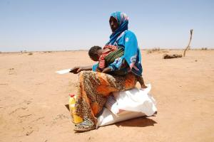 A Somali Mother guards her Child and her new supply of meals from the CHRF Team and Donors!