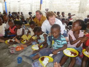 Ken McGrath and Brant Doner provide meals to the children in the refugee camp for Christmas.