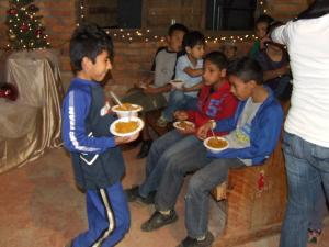 Manuel feeds other children at a special feeding event  near the orphanage.