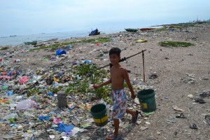 This boy carries water through miles of garbage that is his village.