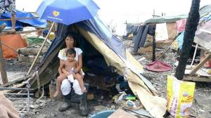 A mother lives in a make-shift tent with her children after her home has burnt down.