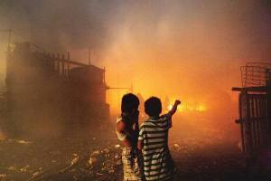 Two children watch as their homes and school building burn to the ground.
