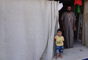 Three Syrian refugee families must share this small room. This man's wife amd brptjer died when their home was hit by a rocket.