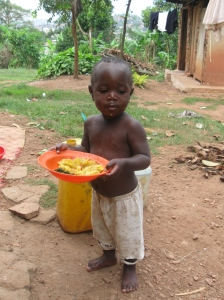 A happy child in Uganda now with a hot meal!