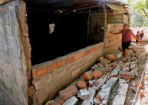 One Mother inspects the damage to her house. She must now find safe shelter and food for her family.