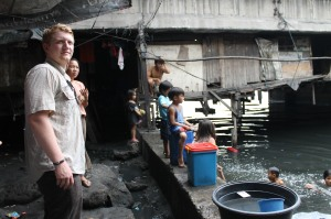 """A CHRF Board Member looks over the horrifying site of a """"bridge community"""" as hundreds of people are forced to live in tiny, dirty and dangerous spaces in the Philippines."""