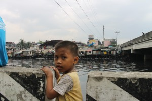 A child stands in front of his community that is overflowing, dirty and dangerous.